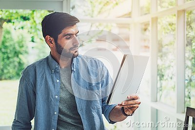 A man looking at paper note while working