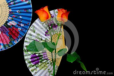 Pair of caribbean orange roses with oriental paper fans background