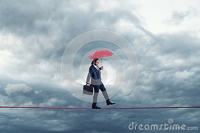 Businessman is walking on a thiny rope, metaphoring risky business life an capability of solving problems in balance.