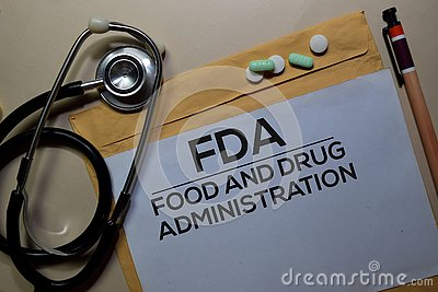 FDA - Food and Drug Administration text on document above brown envelope and stethoscope. Healthcare or medical concept