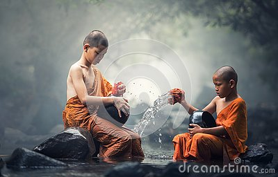 Asian Novice monks cleaning alms bowl