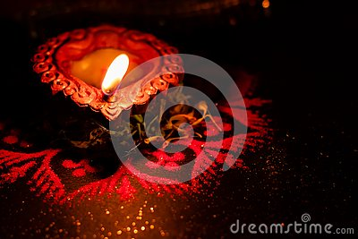 One lit earthen lamp with flame used in Hindu religiion for worship, representing devotional and hope concept