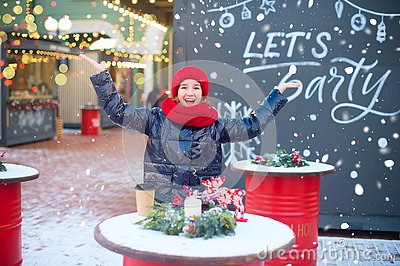 Hally european teenage girl laugh and drop snowflakes in air. Model is on christmas fair. Happy holidays