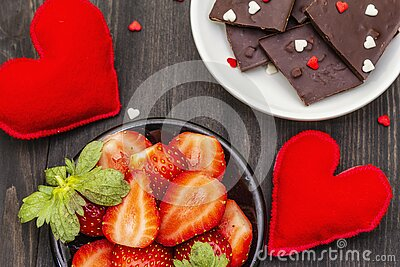 Valentine`s Day romantic concept. Chocolate, fresh ripe strawberry, red felt hearts. Sweet dessert for lovers. Black wooden