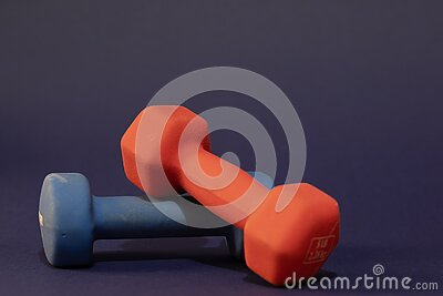 Hand weights, red and blue, each of Five pounds, close-up and isolated on dark blue background