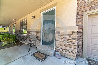 Home with green door yard windows and porch bench against stone brick wall