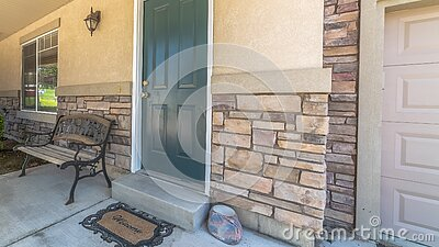 Panorama Home with green door yard windows and porch bench against stone brick wall
