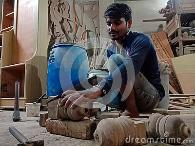 an indian worker making furniture at workshop, iron blade equipment aviable for wood chopping in factory in India January 2020