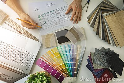 designer working in office doing furniture and flooring material selection from samples for home interior design project