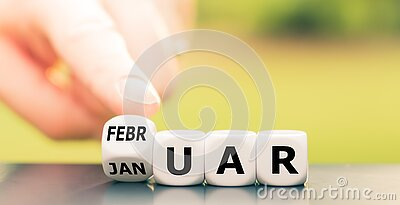 Hand turns a dice and changes the German word `Januar` `January` in English to `Februar` `February` in English.