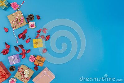 gift box, small pink rose, dried red leaves and pine cone put on the left of picture and space on the right on blue