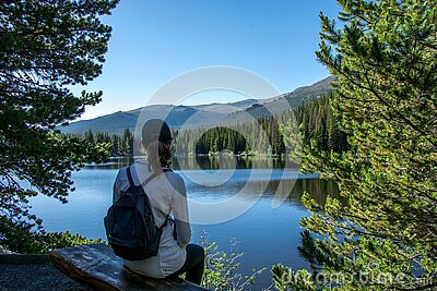 woman sitting at bear lake in spring summer in the rocky mountain national park, colorado united states of america
