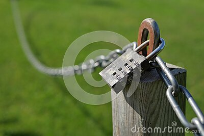 Combination lock secures a chain attached to a wooden post
