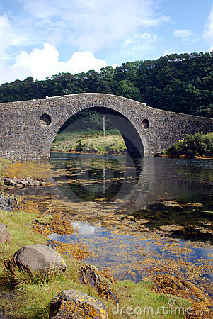 Arched stone bridge over river