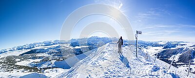 Snow shoe hiker a the summit of the snowy mountain. panoramic picture of winter hiker at the top of the hill. gorgeous swiss alps