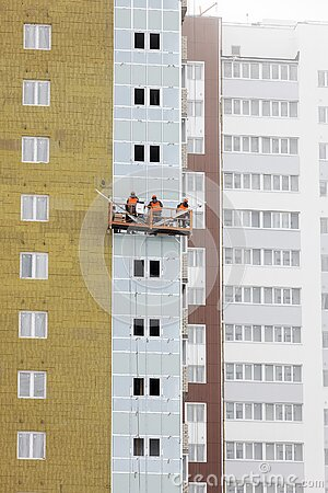 High-rise building under construction. Builders are engaged in external furnish of the walls