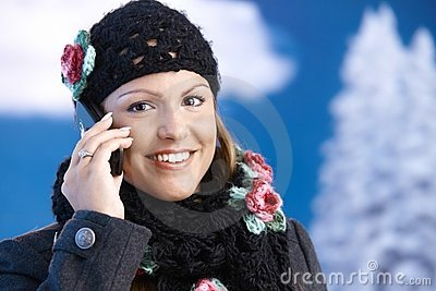Pretty girl dressed up warm smiling using mobile