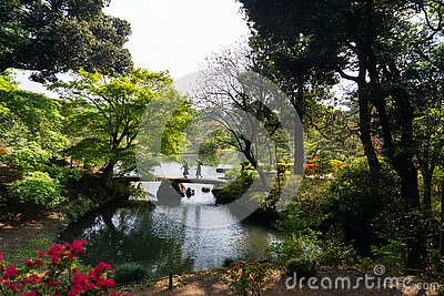 Japanese garden and bridge crossed by two friends