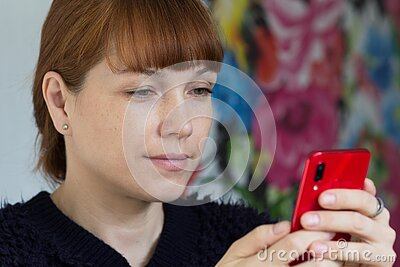 Portrait of the cute smiling middle aged woman looking at mobile phone