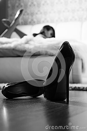High heels in front of female bedroom defocused. Sexy erotic woman relaxing on bed. Attractive female relax. Erotic