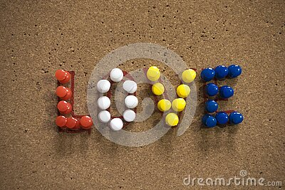 Colorful Love text written with thumbtacks on cork board for Valentine`s Day