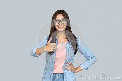 Happy young indian girl look at camera show thumbs up on gray studio background