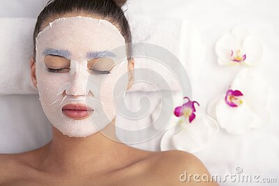 Woman with cotton face mask in beauty salon