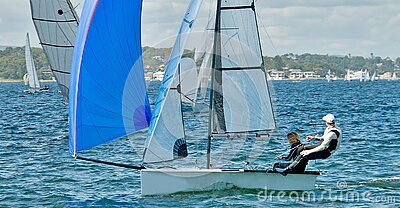 Children sailing racing small sailboat with a blue spinaker on a coastal lake. Commercial use photo