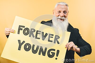 Happy youthful senior feeling forever young - Hipster mature man giving message with yellow banner