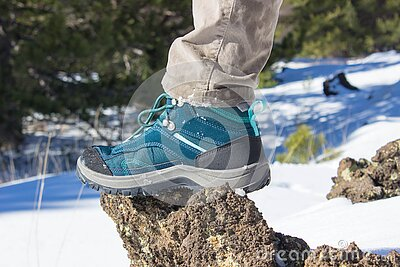 Top view of trekking shoes on the lava stone and snow background, female legs