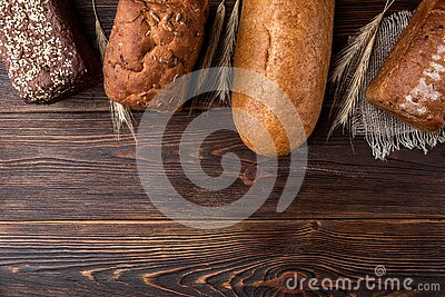 Wheat products on dark wooden. Bread and loaf. Carbohydrates.