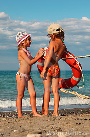 Little sisters in swimsuits standing on beach