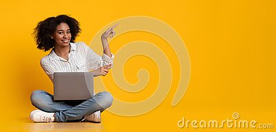 Happy Woman With Laptop Pointing At Copy Space Over Yellow Background