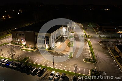 Aerial photo office building and parking lot at night