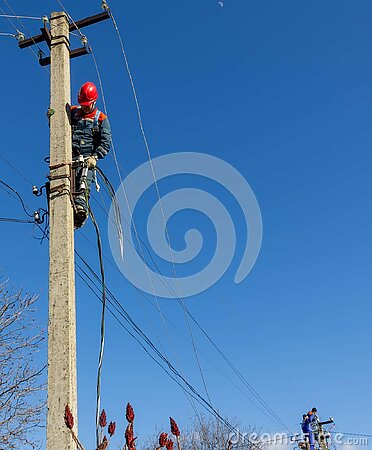 Male electricians on poles mount a new line of electrical wires against a blue sky with a copy space