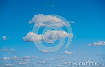 Wide shot of a beautiful bright blue sky with fluffy clouds