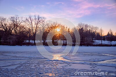 Evening sun overlooking a frozen pond lit with pink sunset sun rays through bare trees branches in Unionville, Markham