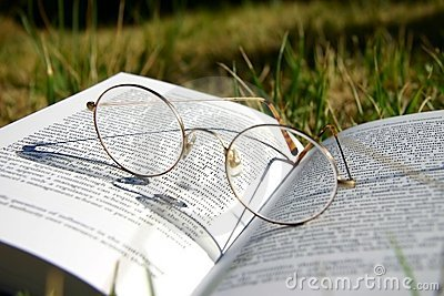 Glasses on a book with grass