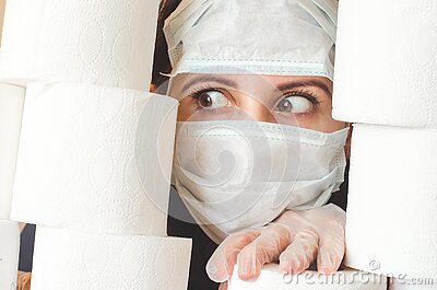 Young woman with scared eyes in two medical virus protection face masks looks through stacks of toilet paper. Covid-19 quarantine