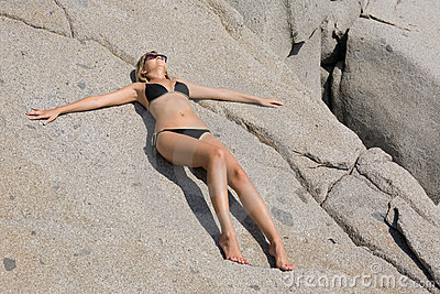 Attractive girl relaxing rocky beach by the sea.