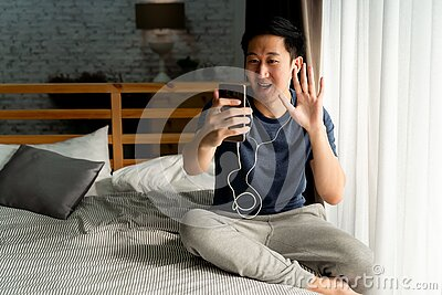 Portrait of happy 30s aged Asian man in casual clothing making facetime video calling with smartphone at home. He`s