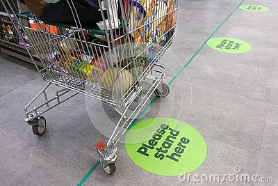 Social distancing marks on supermarket floor intended to stop or slow down the spread of a contagious Coronavirus COVID-19