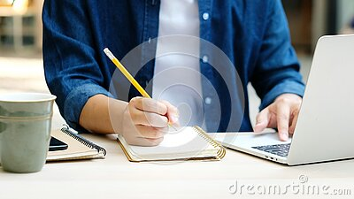 Online education learning, Work from home, Man hand writing on notebook while using laptop computer, Adult male student study