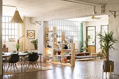 Home indoors. Open space with living room and dining room in bright industrial loft with green plants.