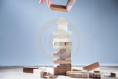 Hand of businessman holding wooden blcoks and wooden house and blocks of wood isolated on gray background. Strategy as business