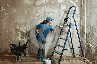 A young woman in a blue t-shirt and a baseball cap makes repairs in the apartment.