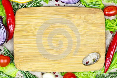 Top view of brown wooden cutting board with summer vegetables and champignon mushroom on table background.