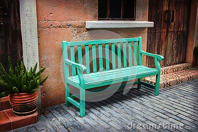 A green bench rests on the sidewalk. By the wall