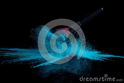 Blue makeup powder brush fall on shiny black surface in a dust cloud