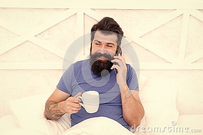Hello dear. Bearded man using mobile technology in bed. Handsome guy talking on phone and drinking coffee at home